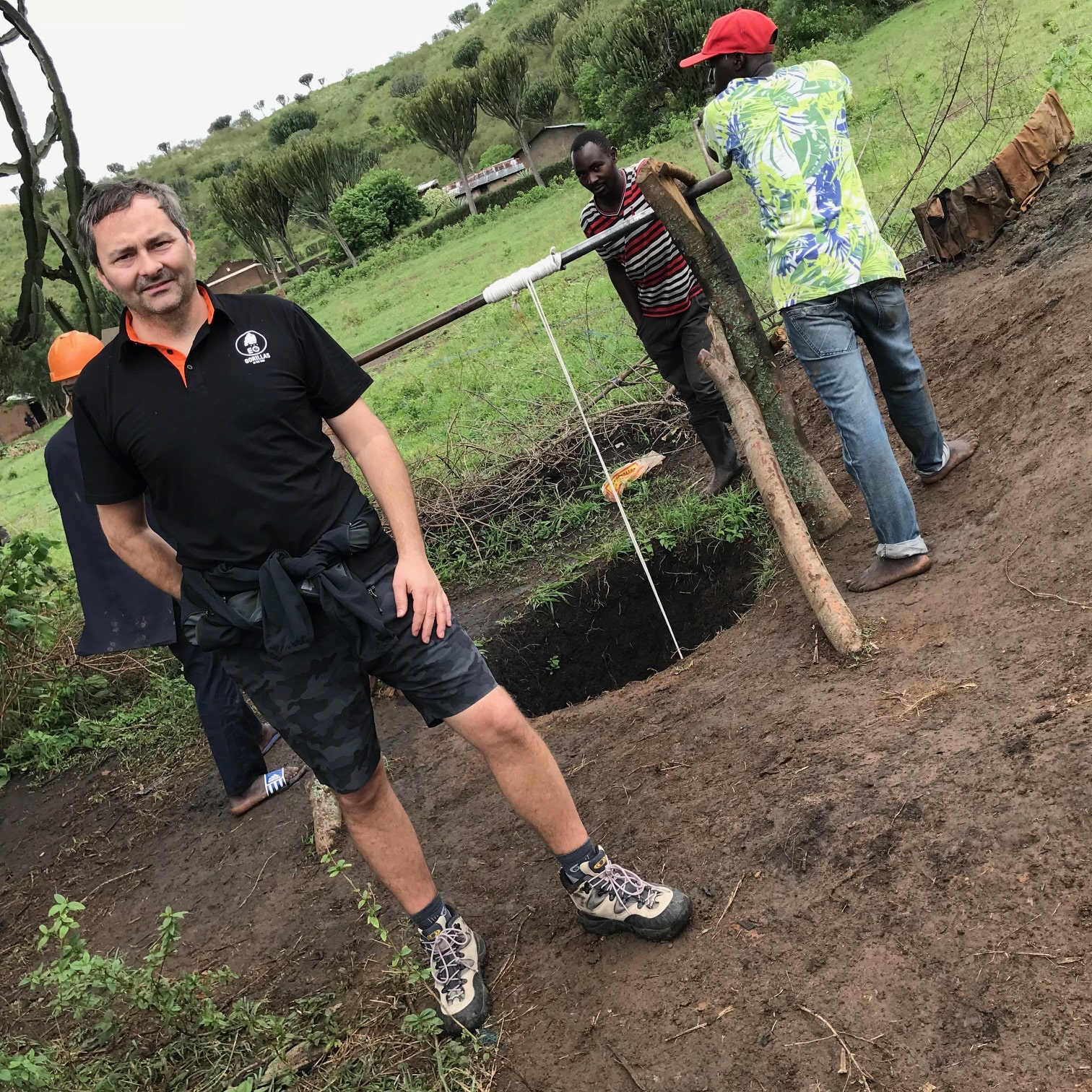 Bedrock Realty owner John Savard is pictured in front of a well being built in Uganda, with community workers behind him