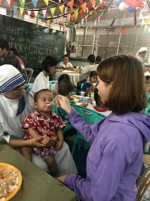 A young girl feeds a baby orphan being held by a nun in the Philippines
